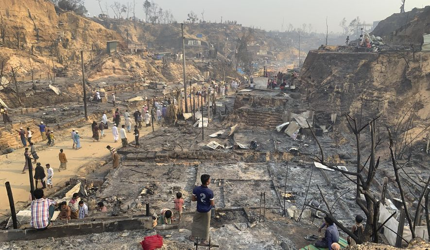 Rohingya refugees look at the remains of Monday's fire at the Rohingya refugee camp in Balukhali, southern Bangladesh, Tuesday, March 23, 2021. The fire destroyed hundreds of shelters and left thousands homeless, officials and witnesses said. (AP Photo/ Shafiqur Rahman)