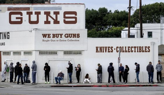 FILE - In this March 15, 2020, file photo, people wait in line to enter a gun store in Culver City, Calif. California could expand its law requiring unique identifiers on every bullet casing to include weapons used by law enforcement, a move that proponents said is another attempt to help investigate shootings by police. (AP Photo/Ringo H.W. Chiu, File)