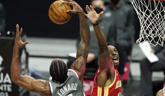 Los Angeles Clippers forward Kawhi Leonard, left, grabs a rebound away from Atlanta Hawks forward Onyeka Okongwu during the first half of an NBA basketball game Monday, March 22, 2021, in Los Angeles. (AP Photo/Mark J. Terrill)
