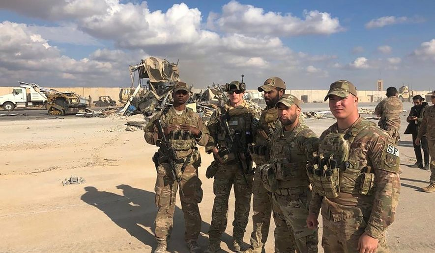 In this Jan. 13, 2020, file photo, U.S. soldiers stand at a site of Iranian bombing at Ain al-Asad air base in Anbar, Iraq. On Tuesday, March 23, 2021, Iraqi officials said Iraq has sent a formal request to President Joe Biden's administration for a date to resume strategic talks on bilateral relations and the withdrawal of remaining U.S. combat forces. The talks, which began in June under the Trump administration, would be the first under Biden, who assumed office in January. (AP Photo/Qassim Abdul-Zahra, File)