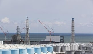 FILE - In this Feb. 27, 2021, file photo, the Pacific Ocean looks over nuclear reactor units of No. 3, left, and 4 at the Fukushima Daiichi nuclear power plant in Okuma town, Fukushima prefecture, northeastern Japan. Japan on Tuesday, March 23,  asked the International Atomic Energy Agency to provide support to safely carry out an imminent release of the massive amounts of treated but still radioactive water stored at the wrecked Fukushima nuclear power plant and to gain understanding from the international community. (AP Photo/Hiro Komae, File)