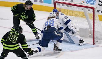 Dallas Stars left wing Roope Hintz (24) shoots between Tampa Bay Lightning's Mikhail Sergachev (98) and Andrei Vasilevskiy (88) to score during the first period of an NHL hockey game in Dallas, Tuesday, March 23, 2021. (AP Photo/Tony Gutierrez)