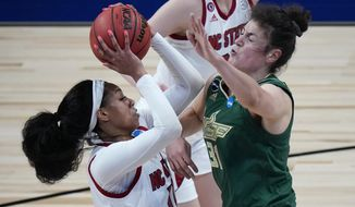 North Carolina State forward Jakia Brown-Turner, left, shoots over South Florida center Beatriz Jordao (31) during the first half of a college basketball game in the second round of the women's NCAA tournament at the Alamodome in San Antonio, Tuesday, March 23, 2021. (AP Photo/Eric Gay)