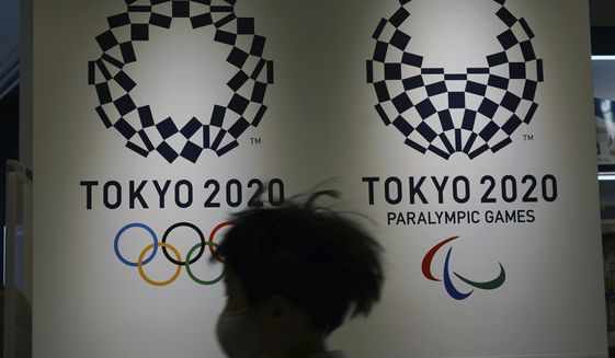 FILE - In this Feb. 23, 2021, file photo, a child wearing a protective mask to help curb the spread of the coronavirus runs in front of the logos of the Tokyo 2020 Olympic and Paralympic Games in Tokyo. Tokyo Olympic organizers and the IOC on Saturday, March 20, 2021 announced a ban on fans from abroad attending the the games, which open on July 23. (AP Photo/Eugene Hoshiko, File)