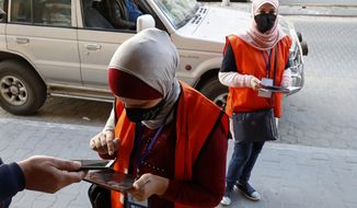 FILE - In this Feb. 10, 2021 file photo, poll workers from the Central Elections Commission register a local resident to the electoral roll, on the main road of Gaza City. Palestinian President Mahmoud Abbas' Fatah party and his militant Hamas rivals would each fall well short of a parliamentary majority if elections are held in May, forcing them to partner with each other or smaller parties to form a government, according to a poll released Tuesday, March 23, 2021, by the Palestinian Center for Policy and Survey Research. (AP Photo/Adel Hana, File)