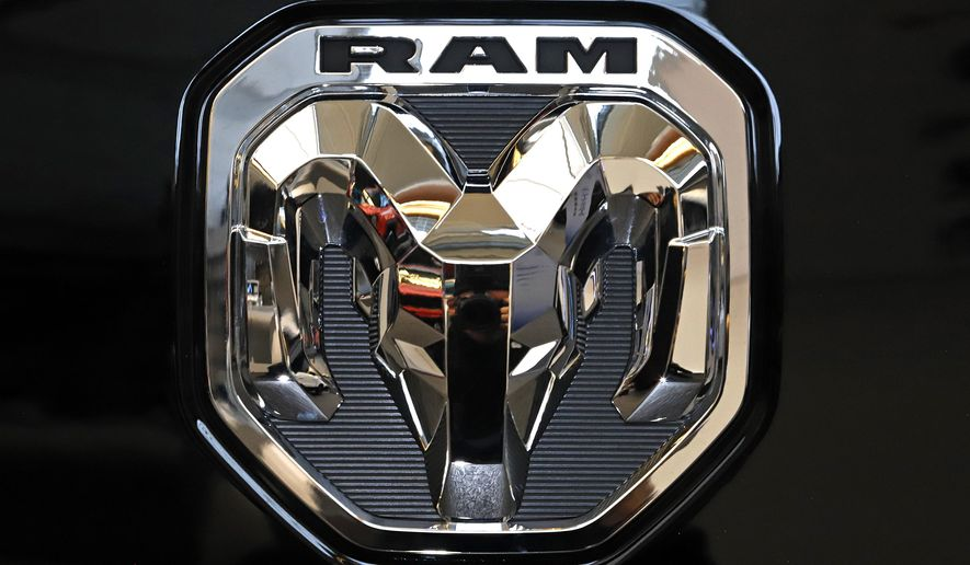 FILE - This Feb. 13, 2020 photo shows the Ram truck logo at the 2020 Pittsburgh International Auto Show in Pittsburgh.  The company that makes heavy-duty diesel Ram trucks is telling some owners to park them outdoors due to the risk of an engine fire. Fiat Chrysler, now part of Stellantis, is recalling just over 20,000 of the trucks mainly in the U.S. and Canada.   (AP Photo/Gene J. Puskar)