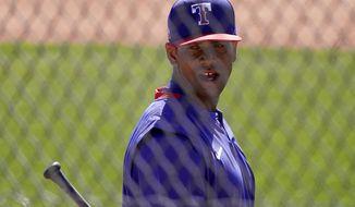 Texas Rangers' Khris Davis waits to bat during spring training baseball practice Monday, Feb. 22, 2021, in Surprise, Ariz. (AP Photo/Charlie Riedel)