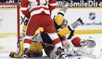 Nashville Predators right wing Viktor Arvidsson (33) falls into Detroit Red Wings goaltender Thomas Greiss (29) after Greiss stopped a shot during the second period of an NHL hockey game Tuesday, March 23, 2021, in Nashville, Tenn. (AP Photo/Mark Zaleski)