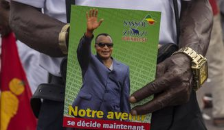 FILE - In this Friday March 19, 2021 file photo, a supporter of President Denis Sassou N'Guesso holds his photo during the last rally of the presidential campaign in Brazzaville, Congo. Republic of Congo pressed ahead Sunday March 21, 2021 with an election in which President Denis Sassou N'Guesso is widely expected to extend his 36 years in power, while the leading opposition candidate was flown to France after suffering COVID-19 complications. (AP Photo/Zed Lebon, File)