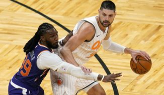 Orlando Magic center Nikola Vucevic, right, looks to get around Phoenix Suns forward Jae Crowder during the second half of an NBA basketball game, Wednesday, March 24, 2021, in Orlando, Fla. (AP Photo/John Raoux)
