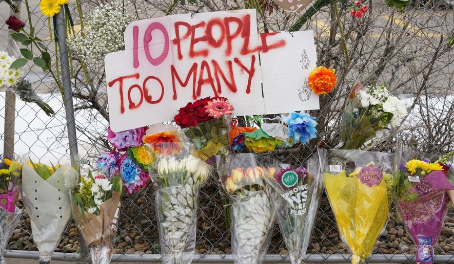 A sign stands above floral bouquets lined along the temporary fence around a King Soopers grocery store, which is where 10 victims died on Monday in a mass shooting, Wednesday, March 24, 2021, in Boulder, Colo. (AP Photo/David Zalubowski)
