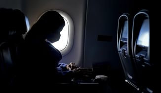 FILE - In this Wednesday, Feb. 3, 2021, file photo, a passenger wears a face mask she travels on a Delta Air Lines flight after taking off from Hartsfield-Jackson International Airport in Atlanta. Airlines are dropping some of the temporary service changes they made during the early part of the coronavirus pandemic. Delta is the only airline still blocking middle seats, but there's no guarantee that'll continue past April 30. (AP Photo/Charlie Riedel, File)