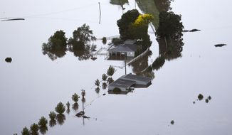 Buildings are partially submerged as floodwater covers large areas northwest of Sydney, Australia, Wednesday, March 24, 2021. Some 18,000 residents of Australia's most populous state have fled their homes since last week, with warnings the flood cleanup could stretch into April. (Lukas Coch/Pool Photo via AP)
