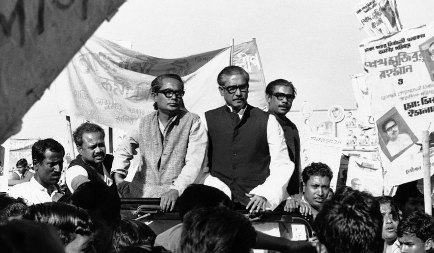 FILE- In this Dec. 7, 1970, file photo, Sheikh Mujibur Rahman, center on Rostrum, leader of East Pakistan's powerful Awami League, addresses an election rally in Dacca, East Pakistan. A watershed moment occurred in 1970 amid strikes and rising hostilities, when East Pakistan's Awami League, led by Bengali politician Sheikh Mujibur Rahman, swept the polls in a national election. The government rejected the results, spawning a civil disobedience movement. On March 26, 1971, Bangladesh declared independence, sparking the nine-month war. Pakistan launched a military operation to stop the move to independence, while India joined on the side of what is now Bangladesh. Pakistani forces surrendered on Dec. 16, 1971. (AP Photo/Dennis Lee Royle, File)