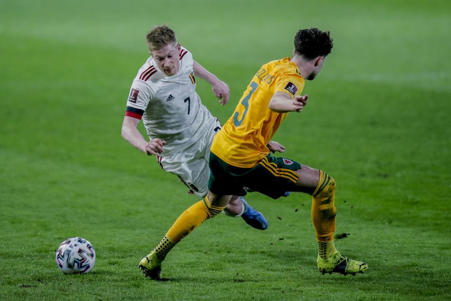 Belgium's Kevin De Bruyne, left, vies for the ball with Wales' Neco Williams during a World Cup 2022 group E qualifying soccer match between Belgium and Wales at the King Power stadium in Leuven, Belgium, Wednesday, March 24, 2021. (AP Photo/Francisco Seco)