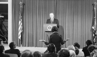 FILE - In this Oct. 9, 1975, file photo President Gerald Ford listens to a news reporter's question during a news conference at the Executive Office building in Washington. It was Ford's first live nationally broadcast news conference since June 24. (AP Photo, File)