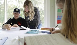 FILE - In this Oct. 9, 2019, photo, Donya Grant, center, works on a homeschool lesson with her son Kemper, 14, as her daughter Rowyn, 11, works at right, at their home in Monroe, Wash. The rate of households homeschooling their children doubled from the start of the pandemic last spring to the start of the new school year last September, according to a new U.S. Census Bureau report released this week. (AP Photo/Ted S. Warren, File)