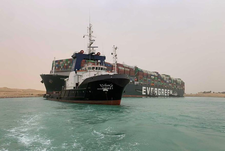 In this photo released by the Suez Canal Authority, a boat navigates in front of a cargo ship, Ever Given, Wednesday, March 24, 2021, after it becomes wedged across Egypt's Suez Canal and blocked all traffic in the vital waterway. An Egyptian official warned Wednesday it could take at least two days to clear the ship. (Suez Canal Authority via AP)