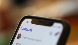 In this Aug. 11, 2019, file photo an iPhone displays a Facebook page in New Orleans.   Facebook says hackers in China used fake accounts and impostor websites in a bid to break into the phones of Uyghur Muslims, Facebook announced Wednesday, March 24, 2021.  (AP Photo/Jenny Kane, File). **FILE**