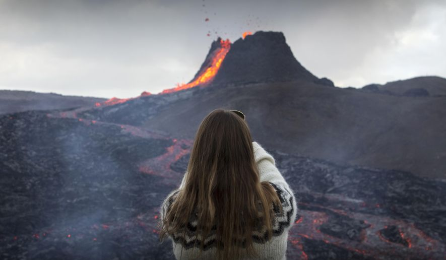 A woman takes a photo as lava flows from an eruption of a volcano on the Reykjanes Peninsula in southwestern Iceland on Tuesday, March 23, 2021. Iceland's latest volcano eruption is quickly attracting crowds of people hoping to get close to the gentle lava flows. The eruption in Geldingadalur, near Iceland's capital Reykjavik, is not seen as a threat to nearby towns and the slow flows mean people can get close to action without too much harm. (AP Photo/Marco Di Marco)