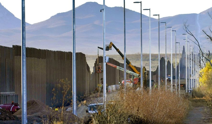 In this Dec. 8, 2020, photo, crews construct a section of border wall in San Bernardino National Wildlife Refuge in Douglas, Ariz. A small town in Arizona has declared a state of emergency over migrant families being dropped there as a growing number of border communities grapple with how to get the families to shelters in bigger cities that can help them. Gila Bend Mayor Chris Riggs made the declaration Tuesday, March 23, 2021, saying the town does not have the resources or funds to support migrants, many who arrive with hopes of seeking asylum and making their home in America. (AP Photo/Matt York) **FILE**