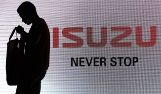 FILE - In this May 11, 2017, file photo, a man walks past the Isuzu logo during the launch of Isuzu MU-X SUV in New Delhi, India. Japanese automakers Toyota, Isuzu and Hino said Wednesday, March 24, 2021 they are setting up a partnership in commercial vehicles to work together in electric, hydrogen, connected and autonomous driving technologies. (AP Photo/Tsering Topgyal, File)