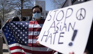 Lucy Lee, of Marietta, Ga., holds an American flag while rallying outside of the Georgia State Capitol in Atlanta during a unity 'Stop Asian Hate' rally Saturday afternoon, March 20, 2021. (AP Photo/Ben Gray)