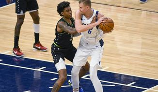 Minnesota Timberwolves forward Jaden McDaniels (3) tries to slap the ball away from Dallas Mavericks center Kristaps Porzingisduring the first half of an NBA basketball game Wednesday, March 24, 2021, in Minneapolis. (AP Photo/Craig Lassig)