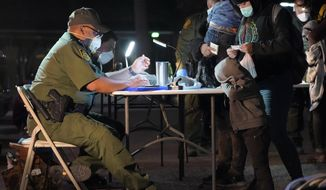 A child rests its head on a table as a U.S. Customs and Border Protection officer processes migrants after they crossed into the U.S., early Wednesday, March 24, 2021, in Roma, Texas. A surge of migrants on the Southwest border has the Biden administration on the defensive. The head of Homeland Security acknowledged the severity of the problem but insisted it's under control and said he won't revive a Trump-era practice of immediately expelling teens and children. (AP Photo/Julio Cortez)