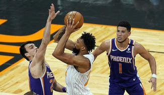 Orlando Magic center Khem Birch, center, gets off a shot against Phoenix Suns forward Dario Saric, left, and guard Devin Booker (1) during the second half of an NBA basketball game, Wednesday, March 24, 2021, in Orlando, Fla. (AP Photo/John Raoux)