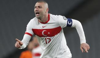 Turkey's Burak Yilmaz celebrates after scoring his side's opening goal during the World Cup 2022 group G qualifying soccer match between Turkey and Netherlands at the Ataturk Olimpiyat Stadium in Istanbul, Turkey, Wednesday, March 24, 2021. (Murad Sezer/Pool Photo via AP)