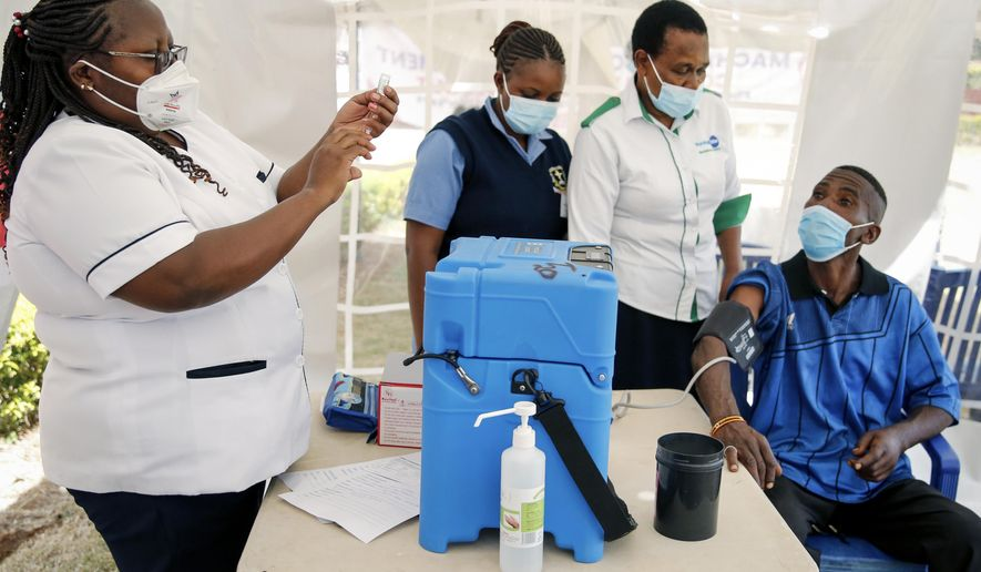 A nurse, left, prepares a shot of AstraZeneca COVID-19 vaccine, manufactured by the Serum Institute of India and provided through the global COVAX initiative, from a portable cold storage box, center, in Machakos, Kenya, Wednesday, March 24, 2021. AstraZeneca's repeated missteps in reporting vaccine data coupled with a blood clot scare could do lasting damage to the credibility of a shot that is the linchpin in the global strategy to stop the coronavirus pandemic, potentially even undermining vaccine confidence more broadly, experts say. (AP Photo/Brian Inganga)