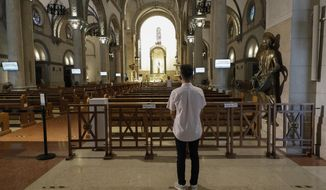 A man prays inside an empty Manila Cathedral, Philippines as they observe strict health protocols to prevent the spread of the coronavirus on Wednesday, March 24, 2021. Presidential spokesman Harry Roque warned Tuesday that the government will forcibly close Roman Catholic churches in the capital if priests proceed with a plan to hold masses in defiance of new restrictions against public meetings, including religious gatherings, to ease an alarming surge in coronavirus infections. (AP Photo/Aaron Favila)