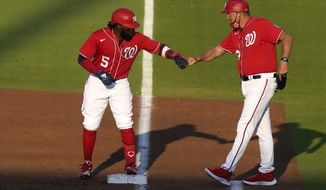 Washington Nationals' Josh Harrison (5) bumps fists with first base coach Randy Knorr after hitting a single during the first inning of a spring training baseball game against the Houston Astros, Wednesday, March 24, 2021, in West Palm Beach, Fla. (AP Photo/Lynne Sladky)