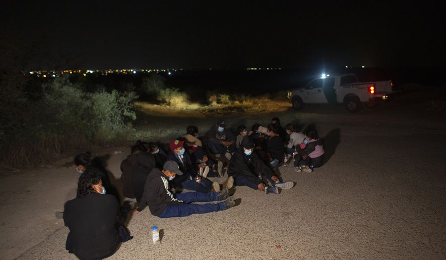 Migrants, mostly from Guatemala, wait at a U.S. Border Patrol intake site after they were smuggled on an inflatable raft across the Rio Grande river in Roma, Texas, Wednesday, March 24, 2021. On Wednesday, President Joe Biden tapped Vice President Kamala Harris to lead the White House efforts at the U.S. southern border and work with Central American nations to address root causes of the migration. The lights of the Mexican city of Miguel Aleman can be seen in the background. (AP Photo/Dario Lopez-Mills)