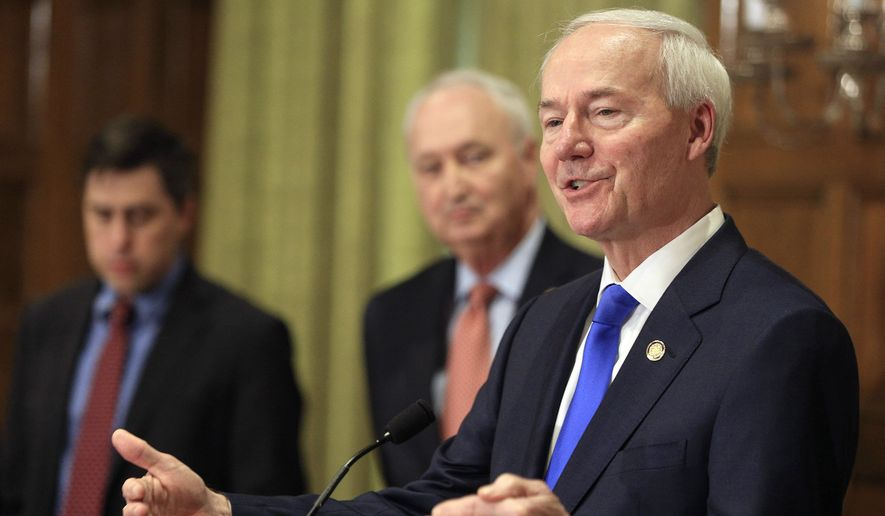 Arkansas Gov. Asa Hutchinson, right, speaks during a news conference in Little Rock, Ark. Gov. Hutchinson on Thursday, March 25, 2021 signed a law banning transgender women and girls from competing in school sports teams consistent with their gender identity. (Staton Breidenthal/The Arkansas Democrat-Gazette via AP)