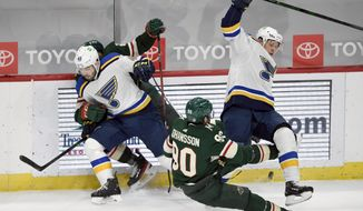 St. Louis Blues' Jake Walman (46) pins Minnesota Wild's Matt Dumba (24) to the boards as Wild's Marcus Johansson (90) and St. Louis Blues' Vladimir Tarasenko (91) fall to the ice during the first period of an NHL hockey game Thursday, March 25, 2021, in St. Paul, Minn. (AP Photo/Hannah Foslien)