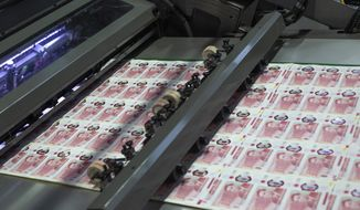 In this photo provided by the Bank of England on Thursday, March 25, 2021, new 50-pound notes featuring scientist Alan Turing on the printing press. The rainbow flag is flying proudly above the Bank of England in the heart of London's financial district to commemorate legendary World War II codebreaker Alan Turing, the new face of Britain's 50-pound note. The design of the banknote, which is the most valuable in circulation, was unveiled Thursday before it is formally issued on June 23, Turing's birthday. (Bank of England via AP)