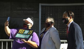"""Aminta Alvarado, left, Mullissa Willette, center, and Assembly member Rob Bonta, right, pose for a photo before a rally for """"Yes on 25"""", a ballot proposition to eliminate the cash bail system in the state on Oct. 13, 2020, in San Francisco. California Gov. Gavin Newsom has nominated Rob Bonta to be the state's next attorney general. (Aric Crabb/Bay Area News Group via AP)"""