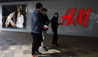 Residents wearing masks pass near a H&M store in Beijing on Thursday, March 25, 2021. China's ruling Communist Party is lashing out at H&M and other clothing and footwear brands as it retaliates for Western sanctions imposed on Chinese officials accused of human rights abuses in the northwestern region of Xinjiang. (AP Photo/Ng Han Guan)