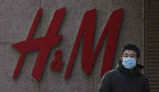 A man wearing a face mask walks by a Swedish fashion brand H&M store outlet in Beijing, Thursday, March 25, 2021. China's ruling Communist Party is lashing out at H&M and other clothing and footwear brands as it retaliates for Western sanctions imposed on Chinese officials accused of human rights abuses in the northwestern region of Xinjiang. (AP Photo/Andy Wong)