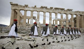 Members of the Presidential Guard walk in front of the Parthenon temple atop of Acropolis Hill before the Greek flag raising ceremony in Athens, Thursday, March 25, 2021. Greece celebrates the bicentenary of the start of the country's war of independence against the Ottoman Empire. (AP Photo/Petros Giannakouris, Pool)