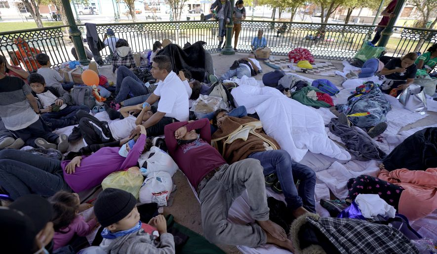 A group of migrants rest on a gazebo at a park after the deportees from the U.S. were pushed by Mexican authorities off an area they had been staying after their expulsion, Saturday, March 20, 2021, in Reynosa, Mexico. The Biden administration says that it's working to address the increase in migrants coming to the border. (AP Photo/Julio Cortez)