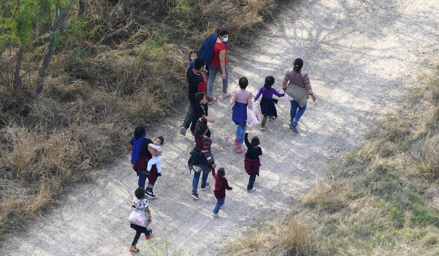 Migrants walk on a dirt road after crossing the U.S.-Mexico border, Tuesday, March 23, 2021, in Mission, Texas. The Biden administration says that it's working to address the increase in migrants coming to the border. (AP Photo/Julio Cortez)