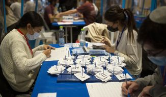 Workers count votes in Israel's national elections wearing and divided in groups by sheets of plastic masks to help curb the spread of the coronavirus, at the Knesset in Jerusalem, Thursday, March 25, 2021. (AP Photo/Maya Alleruzzo)