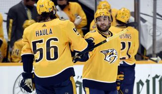 Nashville Predators right wing Rocco Grimaldi (23) is congratulated by left wing Erik Haula (56) after scoring his third goal, for a hat trick against the Detroit Red Wings during the first period of an NHL hockey game Thursday, March 25, 2021, in Nashville, Tenn. (AP Photo/Mark Zaleski)
