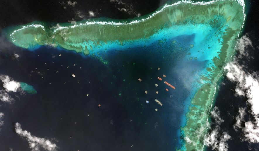 This satellite image provided by Maxar Technologies shows Chinese vessels in the Whitsun Reef located in the disputed South China Sea. Tuesday, March 23, 2021. The United States said Tuesday it's backing the Philippines in a new standoff with Beijing in the disputed South China Sea, where Manila has asked a Chinese fishing flotilla to leave a reef. China ignored the call, insisting it owns the offshore territory. (©2021 Maxar Technologies via AP)