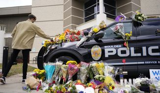 In this March 23, 2021, photo, a man leaves a bouquet on a police cruiser parked outside the Boulder Police Department after an officer was one of the victims of a mass shooting at a King Soopers grocery store in Boulder, Colo. The suspects in the most recent shooting sprees found it relatively easy to get their guns. The suspect in the shooting at a Boulder supermarket was convicted of assaulting a high school classmate but still got a gun.(AP Photo/David Zalubowski)