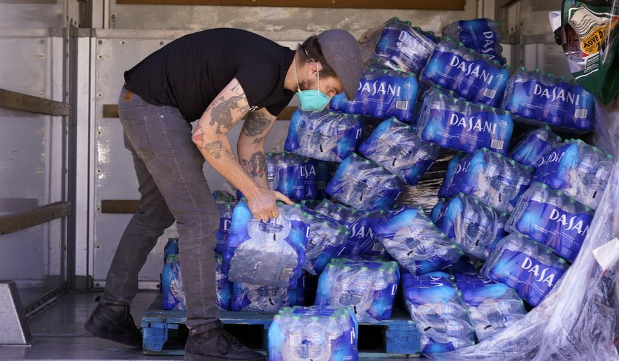 FILE - In this Feb. 23, 2021 file photo, volunteer Ben Harper prepares to hand out drinking water at an apartment complex without water in Dallas. Texas officials on Thursday, March, 25, 2021 raised the death toll from February's winter storm and blackouts to at least 111 people — nearly doubling the state's initial tally following one of the worst power outages in U.S. history. (AP Photo/LM Otero, File)