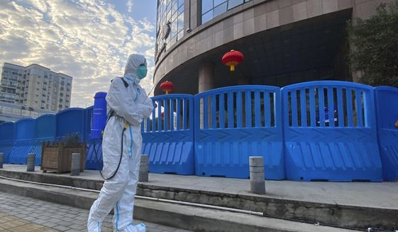 In this photo dated Saturday, Feb. 6, 2021, a worker in protectively overalls and carrying disinfecting equipment walks outside the Wuhan Central Hospital where Li Wenliang, the whistleblower doctor who sounded the alarm and was reprimanded by local police for it in the early days of Wuhan's pandemic, worked in Wuhan in central China. A lengthy written report published Thursday, March 25, 2021, from a team of international and Chinese scientists on a joint mission to Wuhan aims to help unearth the origins of the coronavirus since it was first detected in China more than a year ago. (AP Photo/Ng Han Guan) **FILE**